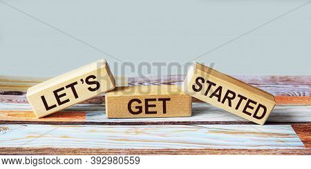 Text Let's Get Started On Wooden Blocks And Colored Background. Business Text, Motivational Quote.