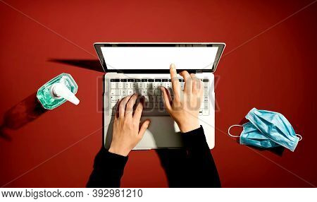 Laptop Computer With Hand Sanitizer And Masks - Overhead View