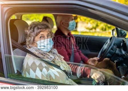 Senior couple wearing protective face masks in their car