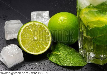 Mojito Cocktail With Ice, Fresh Mint And Lime On A Dark Background, Close-up. A Refreshing Summer Al