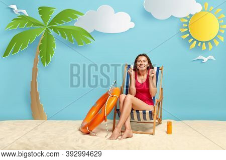 Shot Of Glad Female Vacationist In Red Bikini, Clenches Fists, Enjoys Recreation Time, Poses At Beac