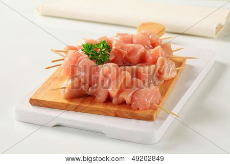 raw poultry skewers on a wooden cutting board
