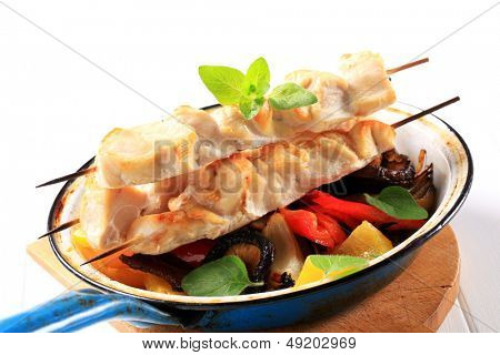 chicken skewers with vegetable side dish in a pan
