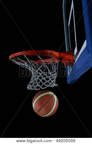 Basketball ball,  board and net  on black background in gym indoor poster