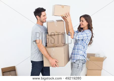 Happy woman giving boxes to her husband while they are moving