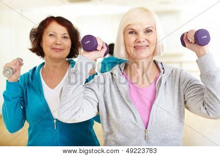 Portrait of sporty females doing physical exercise with barbells in sport gym
