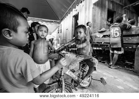 BERDUT, MALAYSIA - APR 8: Unidentified children Orang Asli in his village (b/w photo) on Apr 8, 2013 in Berdut, Malaysia. More than 76% of all Orang Asli live below the poverty line.