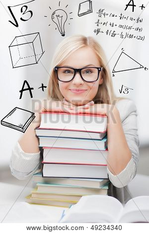 education and school concept - smiling student with stack of books and doodles