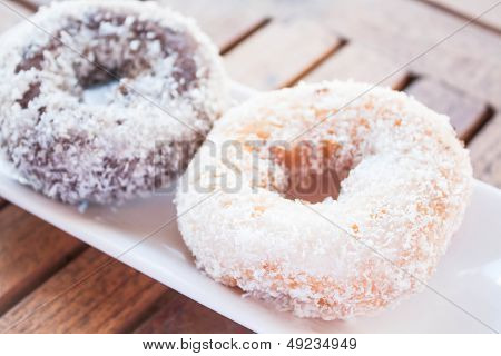 Vanilla And Chocolate Coconut Donuts On Wooden Table