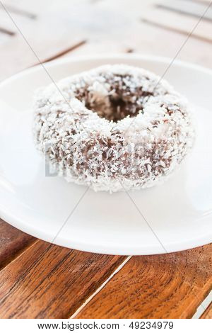 Piece Of Chocolate Coconut Donut On White Plate