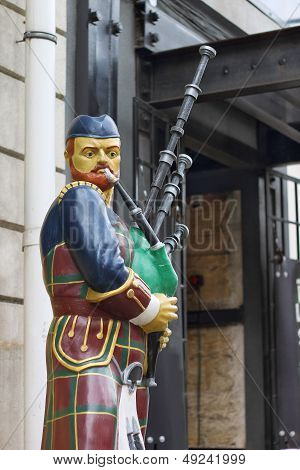 Bagpiper Statue Near The Entrance To The Building.