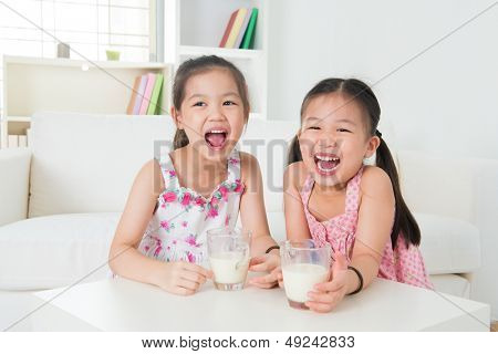 Children drinking milk. Asian family at home. Beautiful sister drinks milk together.