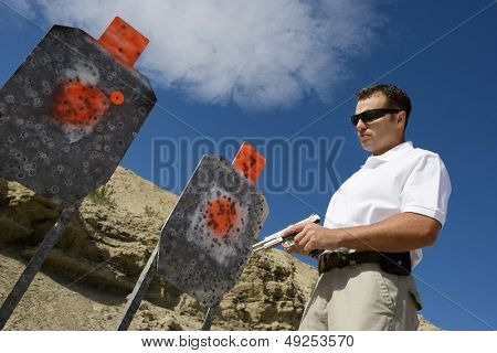 Man holding hand gun near targets at firing range