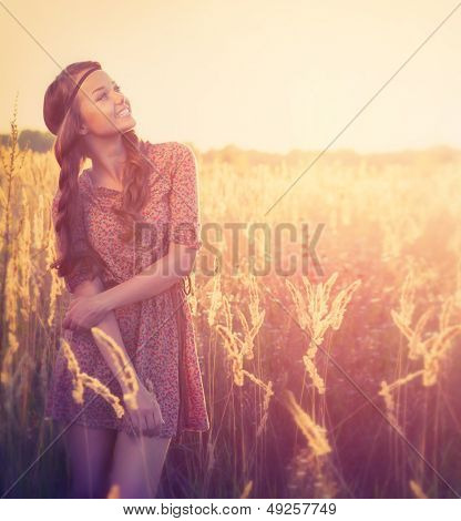Beauty Romantic Girl Outdoors. Beautiful Teenage Model girl Dressed in Fashionable Short Dress Posing on the Field in Sun Light. Glow Sun. Autumn. Toned in warm colors. Copy Space for your text
