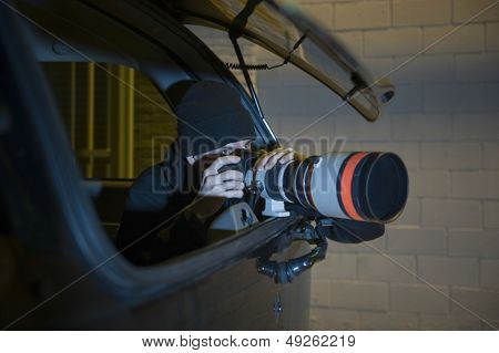 Professional photographer with telephoto lens in car
