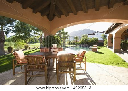 Sitting area with sunlit lawn against mountain