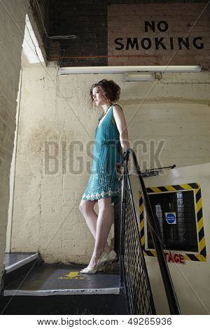 Full length side view of a young woman standing backstage