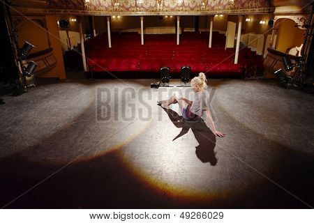 Full length of a young woman reading script on stage