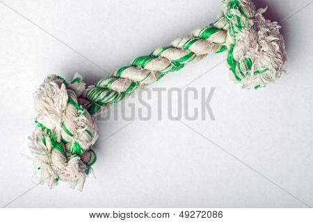 Knotted rope dog toy on white surface