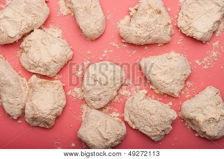 Raw chicken covered in breading against red surface