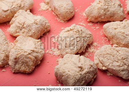 Raw breaded boneless wings against red background