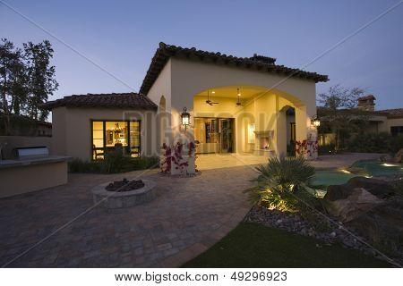 Illuminated house exterior against clear sky at twilight