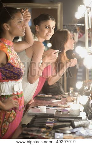 Side view of three multiethnic female models applying makeup in dressing room mirror