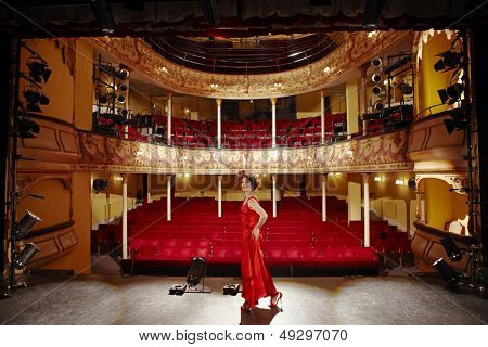 Full length side view of a woman in red gown on stage floor