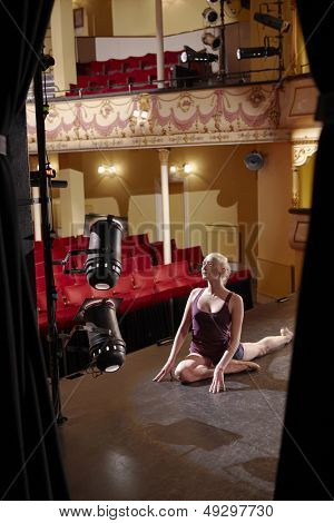 Full length of a young woman stretching on stage