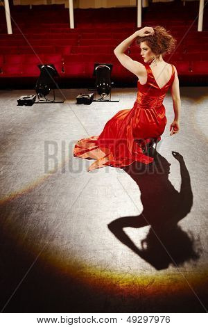 Sensuous young woman in red gown sitting on stage floor
