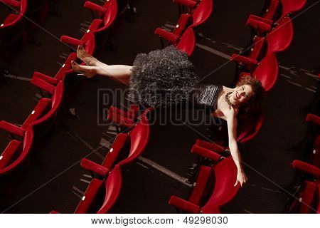 Top view portrait of a smiling young woman lying on theatre stall
