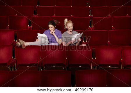 Young women sitting in theatre stall with scripts