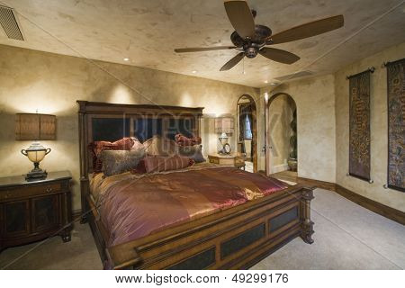 View of a luxury bedroom with silk bedcover on antique bed at home