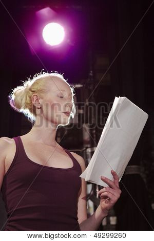 Low angle view of a young woman reading script on stage