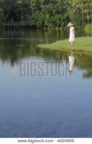 Lady With Sunhat Standing At Water's Edge