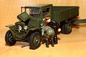Soviet soldier and officer NKVD repair the lorry ZIS-5v. Toy model  of the second world war times. poster