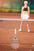 blurred silhouette view of a young woman on clay tennis court outdoors. vertical image poster