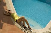 young woman laying on swimming pool edge poster