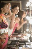 Side view of three multiethnic female models applying makeup in dressing room mirror poster