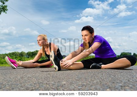 Urban sports - young women doing stretching exercises together before running in the greenfield on a summer day