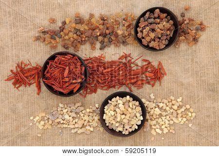 Frankincense, myrrh and sandalwood incense selection over distressed paper background.