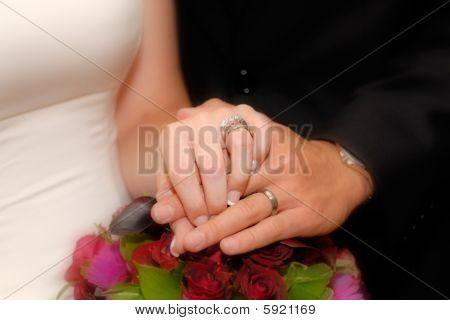 bride and groom holding hands over bouquet of flowers