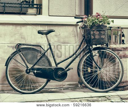 Vintage Stylized Photo Of Old Bicycle Carrying Flowers