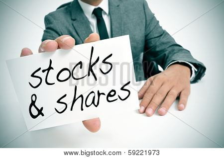 businessman sitting in a desk showing a signboard with the text stocks and shares written in it