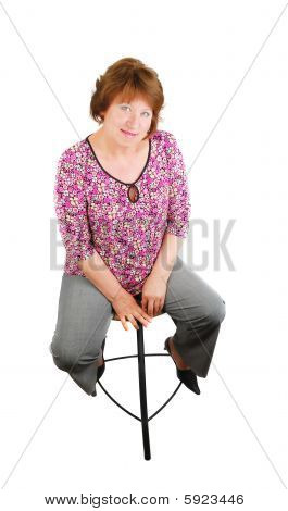 Happy smiling  woman sitting on a bar chair in studio. Happy smiling  woman sitting on a bar chair i