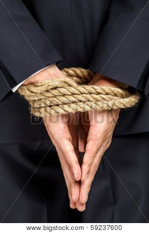 Close up of bound hands of businessman. Concept of slavery and hard work