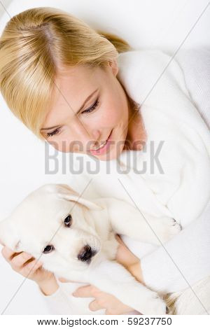 Top view of woman in white sweater with Labrador puppy sitting on her hands poster