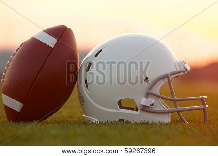 American Football and Helmet on the Field at Sunset poster