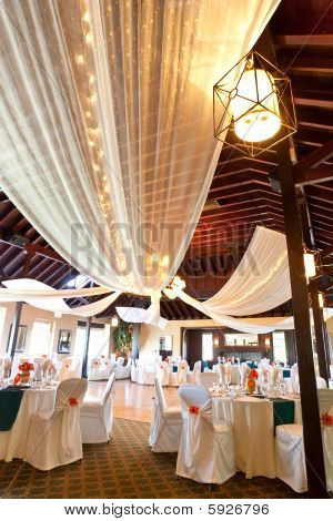 A wide angle view of an wedding reception venue with dance floor and surrounding tables. A large chandelier in the middle of the room has tooling draped from it with mini lights. poster