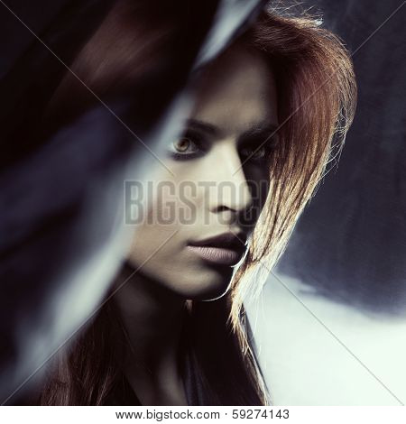 Portrait of young attractive woman in the darkness